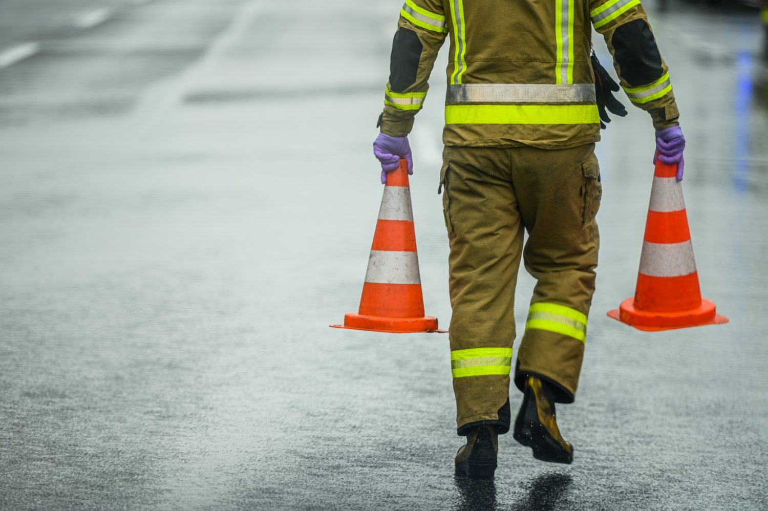 Highway Worker Preparing For Road Closure Moving Two Traffic Cones